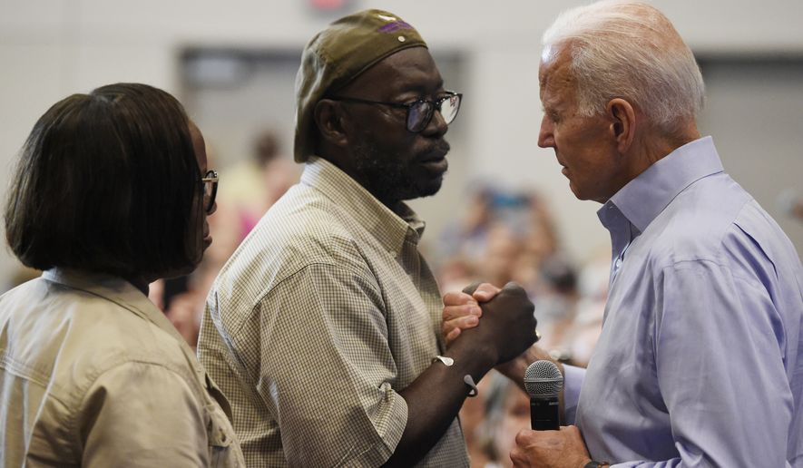 Democratic presidential contender and former Vice President Joe Biden, right, hold hands with Tyrone Sanders, husband of Mother Emanuel shooting survivor Felicia Sanders, left, during a town hall on Sunday, July 7, 2019, in Charleston, S.C. (AP Photo/Meg Kinnard)