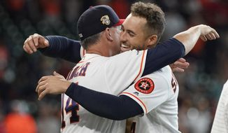 Houston Astros manager AJ Hinch (14) hugs George Springer after Springer's game-ending RBI single against the Los Angeles Angels during the 10th inning of a baseball game Sunday, July 7, 2019, in Houston. The Astros won 11-10. (AP Photo/David J. Phillip)