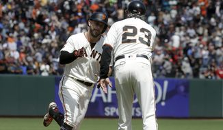 San Francisco Giants' Evan Longoria, left, is congratulated by third base coach Ron Wotus (23) after hitting a solo home run against the St. Louis Cardinals during the seventh inning of a baseball game in San Francisco, Sunday, July 7, 2019. (AP Photo/Jeff Chiu)
