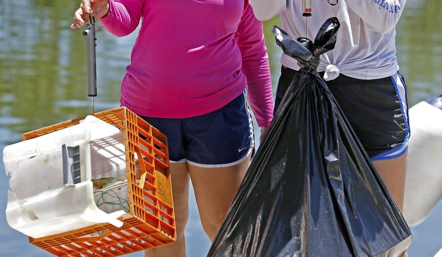 Volunteers for Biscayne National Park Institute, Rebekah Valle and her mother Elizabeth Valle, left to right, weigh the debris they helped pull of sensitive coastal habitats including, sea turtle nesting beaches, mangrove shorelines at Biscayne National Park  in Homestead, Fla., Tuesday, July 2, 2019. (Al Diaz/Miami Herald via AP)