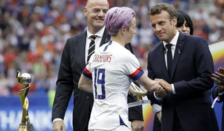 French President Emmanuel Macron, right, and FIFA President Gianni Infantino , left, congratulate to United States' Megan Rapinoe, center, after the Women's World Cup final soccer match between US and The Netherlands at the Stade de Lyon in Decines, outside Lyon, France, Sunday, July 7, 2019. (AP Photo/Alessandra Tarantino)