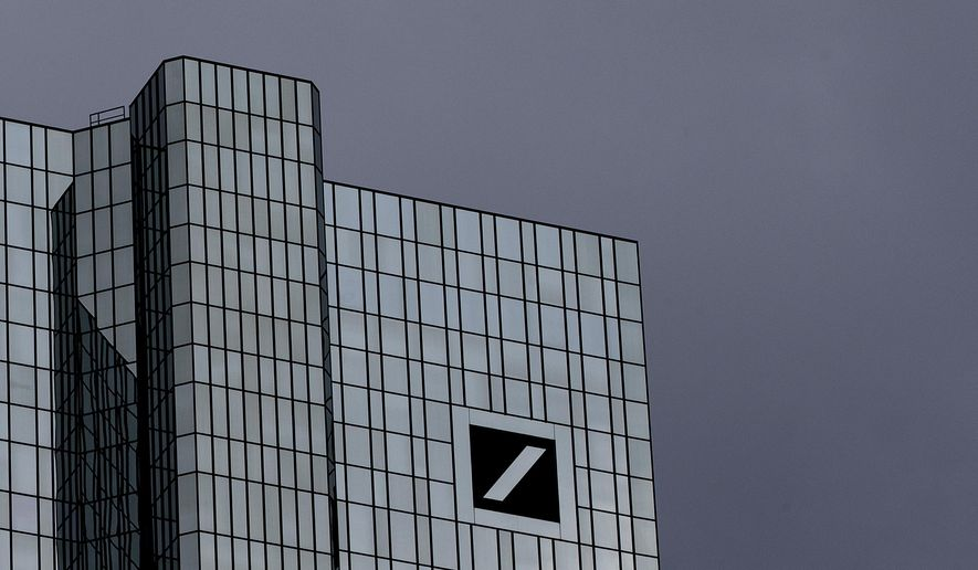 Dark clouds cover the sky over the headquarter of Deutsche Bank in Frankfurt, Germany, Sunday, July 7, 2019. The supervisory board of the bank meets on Sunday to decide about further strategies. (AP Photo/Michael Probst)