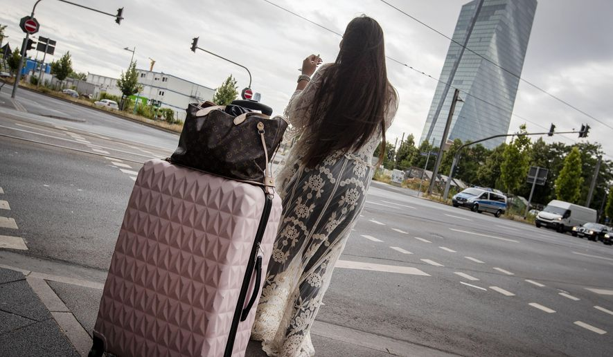 A woman stands with her suitcase near the European Central Bank as 16 000 people are evacuated prior to the defusing of a WWII bomb in Frankfurt, Germany, Sunday, July 7, 2019. The bomb was discovered during construction works right next to the ECB. (AP Photo/Michael Probst)