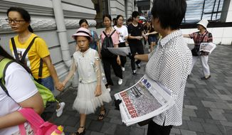 "Hong Kong women distribute newspapers with the headlines ""Millions against Communist China shock the world"" in a shopping district popular with mainland Chinese tourists in Hong Kong Sunday, July 7, 2019. A march was to go through a popular shopping area for Chinese tourists and end at a high-speed rail station that connects the city to the mainland. (AP Photo/Andy Wong)"