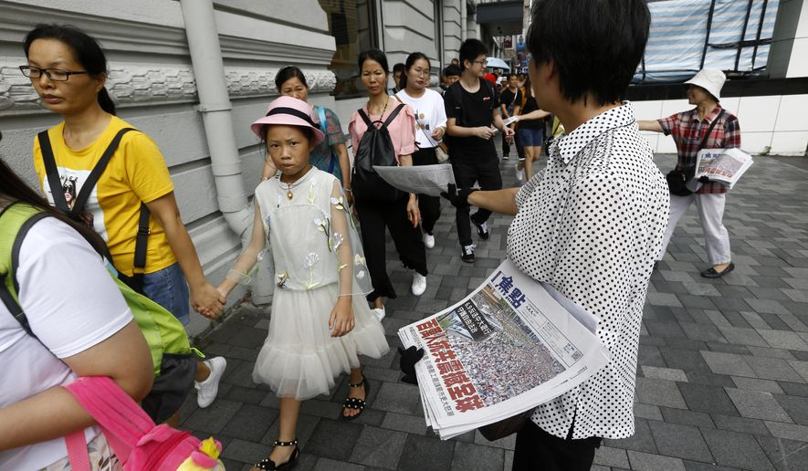 """Hong Kong women distribute newspapers with the headlines """"Millions against Communist China shock the world"""" in a shopping district popular with mainland Chinese tourists in Hong Kong Sunday, July 7, 2019. A march was to go through a popular shopping area for Chinese tourists and end at a high-speed rail station that connects the city to the mainland. (AP Photo/Andy Wong)"""