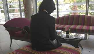 """FILE - In this Oct. 7, 2018, file photo, Grace Meng, the wife of former Interpol President Meng Hongwei, who does not want her face shown, consults her mobile phone in the lobby of an hotel in Lyon, central France, where the police agency is based. Meng Hongwei has sued the international police agency, accusing it of failing to protect him from arrest in China and failing to protect his family. Grace Meng said in a statement on Sunday, July 7, 2019, that her lawyers filed a lawsuit in the Permanent Court of Arbitration in The Hague, Netherlands. She says Interpol """"breached its obligations owed to my family"""" and """"is complicit in the internationally wrongful acts of its member country, China."""" (AP Photo/John Leicester, File)"""