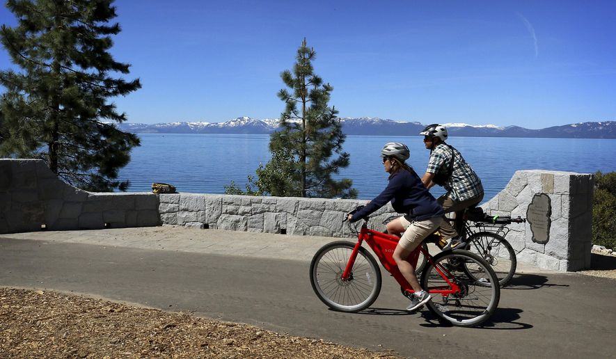 In this June 25, 2019 photo, the Tahoe Fund's CEO Amy Berry, left, and The Reno Gazette-Journal reporter Ben Spillman take a ride on the new Tahoe East Shore Trail near Incline Village, Nev. The Tahoe East Shore Trail that opened Friday (June 28) includes an 810-foot (246-meter) long bridge overhanging the lakeshore between Incline Village and a state park at Sand Harbor. (Jason Bean/The Reno Gazette-Journal via AP)