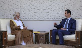 In this photo released by the Syrian official news agency SANA, Syrian President Bashar Assad, right, meets with Oman's Foreign Minister Yusuf bin Alawi, left, in Damascus, Syria, Sunday, July 7, 2019. Alawi made a rare visit to Damascus where he discussed with President Bashar Assad ways of restoring stability and security in the region.(SANA via AP)