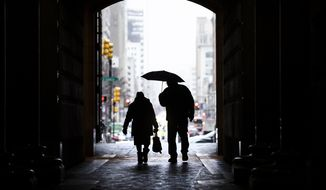 In this Feb. 12, 2019, file photo pedestrians pass beneath City Hall in Philadelphia. Nearly one-quarter of Americans say they never plan to retire, according to a poll that suggests a disconnect between individuals' retirement plans and the realities of aging in the workforce.  (AP Photo/Matt Rourke, File)