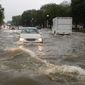 Heavy rainfall flooded the intersection of 15th Street and Constitution Avenue Northwest and stalled cars in the street on Monday in the District. A slow moving weather system dumped 2 to 4 inches of rain. (Associated Press)