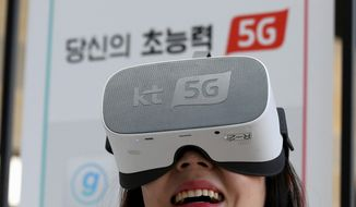 """In this Tuesday, April 2, 2019, file photo, an employee of KT Corp. wears a VR device for an audio-visual experience during a press conference on 5G service at its the headquarters in Seoul, South Korea. South Korea's telecommunications carriers on Wednesday, April 3, have turned on super-fast 5G mobile internet networks abruptly ahead of schedule in an attempt to ensure the country becomes the first in the world to launch the services. The signs read: """"Supernatural Power 5G."""" (AP Photo/Ahn Young-joon)"""