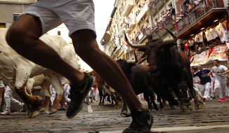 Revellers run next to fighting bulls from Cebada Gago ranch, during the running of the bulls at the San Fermin Festival, in Pamplona, northern Spain, Monday, July 8, 2019. Revellers from around the world flock to Pamplona every year to take part in the eight days of the running of the bulls. (AP Photo/Alvaro Barrientos)