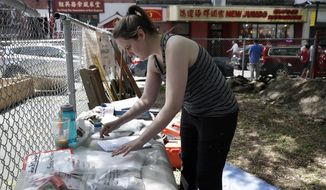 Sarah Keklak, archaeology lab manager for the city of Boston, sorts samples as the first historical excavation takes place, Monday, July 8, 2019, in Boston's Chinatown. The dig is expected to turn up artifacts that will shed new light on immigrants not only from China but also Syria, Ireland and England who sought a new life in Boston from 1840 to 1980. Work is ongoing at a vacant lot near the ornate gate to the colorful neighborhood, and it's expected to continue until early autumn. (AP Photo/Elise Amendola)