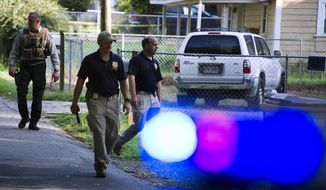 Georgia Bureau of Investigation agents and Hall County Sheriff's Office deputies work a crime scene along Highland Avenue, Monday, July 8, 2019, in Gainesville Ga., where a Hall County Sheriff's deputy was shot the night before. Authorities were searching Monday for suspects after a Georgia sheriff's deputy was killed in a shootout northeast of Atlanta. (Scott Rogers/The Times via AP)