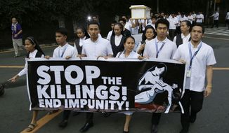 FILE - In this Aug. 29, 2018, file photo, seminarians and nuns carry slogans and a mock coffin during a rally in Manila, Philippines, against drug-related killings and martial law. Amnesty International urgently called Monday for international pressure and an immediate U.N. investigation to help end what it says are possible crimes against humanity in the Philippine president's bloody anti-drug crackdown. (AP Photo/Aaron Favila, File)