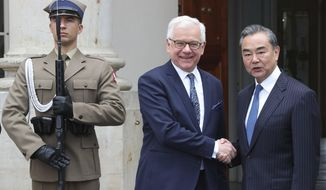Poland's Foreign Minister Jacek Czaputowicz, left, greets his Chinese counterpart Wang Yi, right, for talks on intensifying political and trade relations at the Palace on Water in the Lazienki Park in Warsaw, Poland, Monday, July 8, 2019. (AP Photo/Czarek Sokolowski)