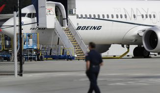 FILE - In this March 14, 2019, file photo, a worker walks next to a Boeing 737 MAX 8 airplane parked at Boeing Field in Seattle. Flyadeal, a Saudi budget carrier says it is ordering 30 new Airbus planes, replacing a $6 billion agreement it had with Boeing for its troubled 737 MAX jets, which are grounded around the world after two crashes. (AP Photo/Ted S. Warren, File)