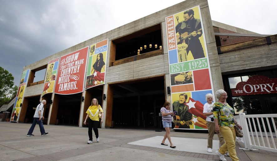 FILE - In this May 1, 2013, file photo, people visit the the Grand Ole Opry House in Nashville, Tenn. A new immersive film showing at the Circle Room explains the history of the Grand Ole Opry while showing video clips of over 100 different artists on stage. The 14-minute film is hosted by Garth Brooks and Trisha Yearwood. (AP Photo/Mark Humphrey, File)