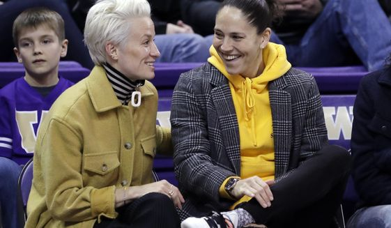 In this Jan. 27, 2019, file photo, Seattle Reign FC soccer player Megan Rapinoe, left, and Seattle Storm's Sue Bird talk during an NCAA college basketball game between Washington and Oregon, in Seattle. On hand as a spectator for Women's World Cup final soccer match in Lyon, France, on Sunday, July 7, 2019, was Rapinoe's girlfriend, Bird. For LGBTQ Americans, many of them frustrated by the lack of openly gay players, the women's soccer team has been a source of pride and celebration. (AP Photo/Elaine Thompson) ** FILE **