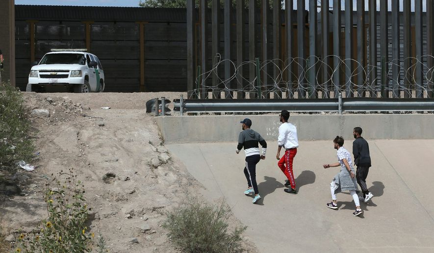 Asylum seekers cross the border between El Paso, Texas, and Ciudad Juarez, Mexico, on Thursday. (Associated Press)