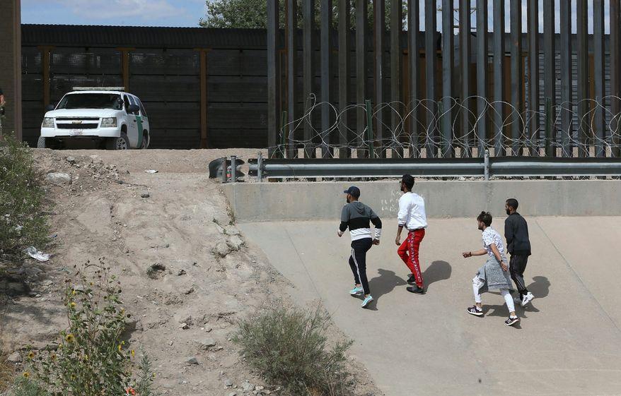Asylum seekers cross the border between El Paso, Texas, and Ciudad Juarez, Mexico, on Thursday. (Associated Press)