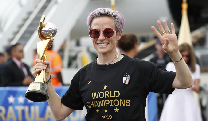 United States women's soccer team member Megan Rapinoe holds the Women's World Cup trophy as she celebrates in front of the media after arriving at Newark Liberty International Airport, Monday, July 8, 2019, in Newark, N.J. (AP Photo/Kathy Willens)