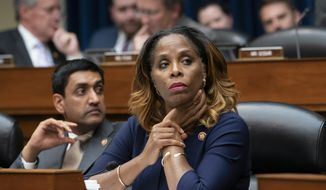 Del. Stacey Plaskett, D-Virgin Islands, joined at left by Rep. Ro Khanna, D-Calif., listen during the roll call as the House Oversight and Reform Committee votes 24-15 to hold Attorney General William Barr and Commerce Secretary Wilbur Ross in contempt for failing to turn over subpoenaed documents related to the Trump administration's decision to add a citizenship question to the 2020 census, on Capitol Hill in Washington, Wednesday, June 12, 2019.  (AP Photo/J. Scott Applewhite)