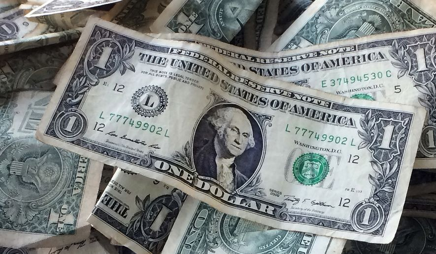 FILE - This Oct. 24, 2016, file photo shows dollar bills in New York. Gradually raising the federal minimum wage to $15 an hour by 2025 would boost pay for as many as 27 million workers, according to a new report. (AP Photo/Mark Lennihan, File)