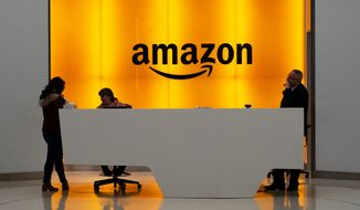In this Feb. 14, 2019, file photo, people stand in the lobby for Amazon offices in New York. Amazon and Microsoft are battling for a $10 billion opportunity to build the U.S. military its first war cloud. (AP Photo/Mark Lennihan, File)