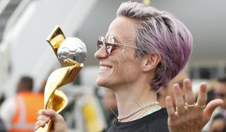 United States women's soccer team member Megan Rapinoe poses with the Women's World Cup trophy as she celebrates with teammates after arriving at Newark Liberty International Airport, Monday, July 8, 2019, in Newark, N.J. (AP Photo/Kathy Willens)
