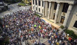 Hundreds attend a rally in front of the Capitol, calling for an override of Gov. Mike Dunleavy's budget vetos on the first day of the Second Special Session of the Alaska Legislature in Juneau on Monday, July 8, 2019. Divided Alaska lawmakers have found little to agree on this year, and that includes where to hold a special session. The Alaska state Senate kicked off its second special session in Juneau on Monday and promptly removed its majority leader, who was 600 miles (965 kilometers) away in Wasilla, with nearly a third of her fellow lawmakers. The first-term governor, a Republican, called for them to meet there, saying said a change of venue to the heart of his conservative base would be good for lawmakers. (Michael Penn/Juneau Empire via AP)