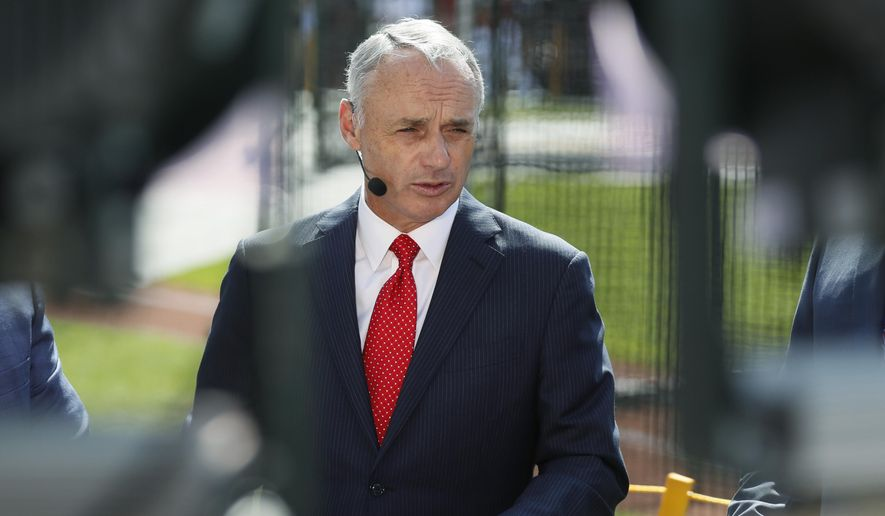 Commissioner Rob Manfred is interviewed as the American League players warm-up for the MLB baseball All-Star Game, Tuesday, July 9, 2019, in Cleveland. (AP Photo/John Minchillo)