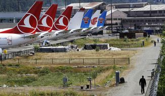 FILE - In this June 27, 2019, file photo people walk a trail past the tails of several of the dozens of grounded Boeing 737 MAX airplanes lining the edge of a parking area adjacent to Boeing Field in Seattle. Boeing Co. reports second quarter deliveries on Tuesday, July 9. (AP Photo/Elaine Thompson, File)