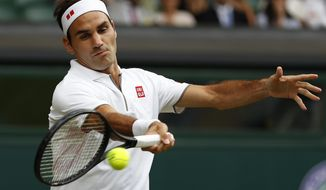 Switzerland's Roger Federer returns the ball to Italy's Matteo Berrettini in a men's singles match during day seven of the Wimbledon Tennis Championships in London, Monday, July 8, 2019. (AP Photo/Alastair Grant)