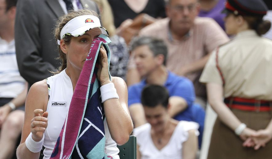 Britain's Johanna Konta wipes her face during a break of a women's quarterfinal match against Czech Republic's Barbora Strycova on day eight of the Wimbledon Tennis Championships in London, Tuesday, July 9, 2019. (AP Photo/Kirsty Wigglesworth)