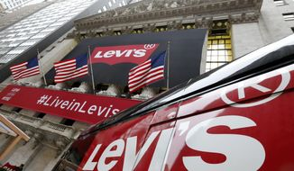 FILE- In this March 21, 2019, file photo a Levi's banner adorns the facade of the New York Stock Exchange. Levi Strauss & Co. reports financial results on Tuesday, July 9. (AP Photo/Richard Drew, File)