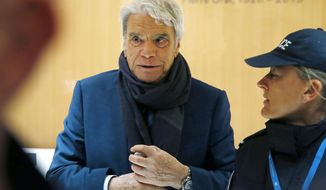 FILE - In this March 13, 2019 file photo, French tycoon Bernard Tapie arrives at Paris court house. A court has acquitted Tuesday July 9, 2019 Bernard Tapie of fraud over a 404 million-euro ($452.5 million at the current exchange rate) payment linked to the sale of sportswear company Adidas in the 1990s. (AP Photos/Michel Euler, File)