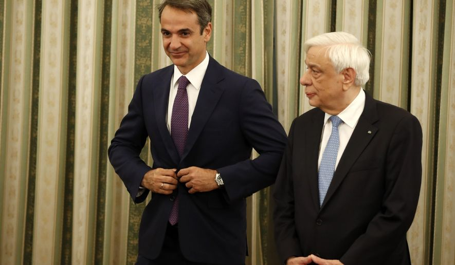 Greece's President Prokopis Pavlopoulos, right, and Prime Minister Kyriakos Mitsotakis attend the swearing ceremony of the new cabinet at the Presidential palace in Athens, Tuesday, July 9, 2019. Cabinet has been sworn in, two days after conservative party leader Kyriakos Mitsotakis won early elections on pledges to make the country more business-friendly, cut taxes and negotiate an easing of draconian budget conditions agreed as part of Greece's rescue program. (AP Photo/Thanassis Stavrakis)