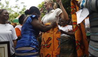 FILE - In this April 17, 2019, file photo, White House senior adviser Ivanka Trump reacts as she is wrapped in fabric that was a gift from the women of Cayat, a cocoa and coffee cooperative, in Adzope, Ivory Coast. Ivanka Trump is applauding the recent passage of legislation in Ivory Coast related to changes she pushed during her April trip to Africa. The country is on the process of updating its family code to make it more equitable to women. (AP Photo/Jacquelyn Martin, File)