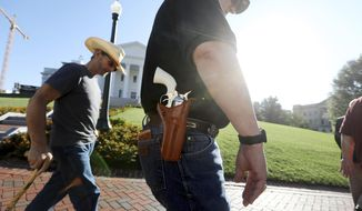 Gun rights supporters walk by the Capitol building in Richmond, Va., on Tuesday, July 9, 2019, the opening for the special session called by Virginia Gov. Ralph Northam. (Steve Earley/The Virginian-Pilot via AP) ** FILE **