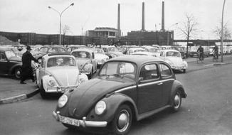 In this April 27, 1966, file photo, Volkswagen workers drive their Beetle cars from the parking lot on their way home at the end of the workday at the world's largest single auto plant, the Volkswagen factory (seen in background) in Wolfsburg, Germany. Volkswagen is halting production of the last version of its Beetle model in July 2019 at its plant in Puebla, Mexico, the end of the road for a vehicle that has symbolized many things over a history spanning eight decades since 1938. (AP Photo, file)
