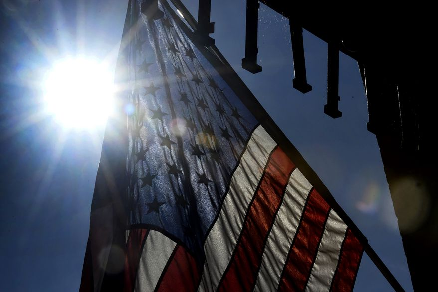 The sun rises behind an American flag posted outside of Petrunik's Kitchen, Door and Moore store at the old Eureka Department store in Windber, Pa., Wednesday, July 10, 2019. (Todd Berkey/The Tribune-Democrat via AP)