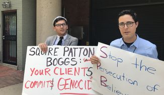 Salih Hudayar (left) and Kyle Olbert rally outside the Squire Patton Boggs offices in D.C. on Wednesday. Save the Persecuted Christians organized demonstrations calling on the firm to stop representing governments that persecute religious minorities. (Photo by Christopher Vondracek/ The Washington Times)