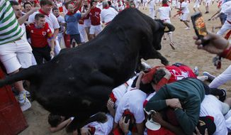 A cow jumps over revellers following the running of the bulls at the San Fermin Festival, in Pamplona, northern Spain, Wednesday, July 10, 2019. Revellers from around the world flock to Pamplona every year to take part in the eight days of the running of the bulls. (AP Photo/Alvaro Barrientos)