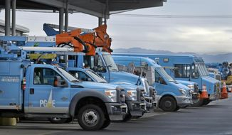 FILE - In this Jan. 14, 2019, file photo, Pacific Gas & Electric vehicles are parked at the PG&E Oakland Service Center in Oakland, Calif. As Pacific Gas & Electric Corp. faces bankruptcy following billions of dollars in claims from catastrophic wildfires, some cities are exploring buying pieces of the utility's assets to run parts of the power system on their own. (AP Photo/Ben Margot, File)