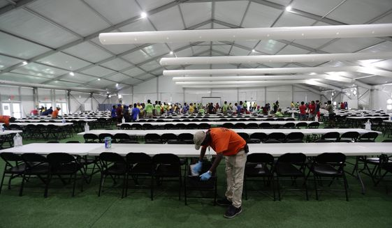 In this July 9, 2019, photo, a staff member cleans in a dining hall at the U.S. government's newest holding center for migrant children in Carrizo Springs, Texas. The government said the holding center will give it much-needed capacity to take in more children from the Border Patrol. (AP Photo/Eric Gay)