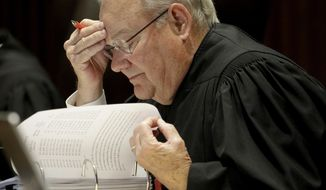 FILE - In this May 9, 2019 file photo, Kansas Supreme Court Justice Lee Johnson looks over documents as he listens to oral arguments in Topeka, Kan. Johnson, whose votes in death penalty cases made him a political target, plans to retire from the bench Sept. 8, 2019. Johnson announced his decision Wednesday, June 10, 2019. (AP Photo/Charlie Riedel File)