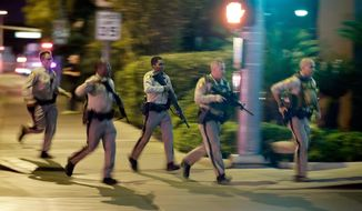 FILE - In this Oct. 1, 2017, file photo, police run toward the scene of a shooting near the Mandalay Bay resort and casino on the Las Vegas Strip in Las Vegas. The head of the Las Vegas police department is scheduled to release what he calls an after-action report about the deadliest mass shooting in modern U.S. history. Clark County Sheriff Joe Lombardo says the review he'll release Wednesday, July 10, 2019, aims to show what other law enforcement agencies can learn from the shooting that killed 58 people and injured more than 850. (AP Photo/John Locher, File)