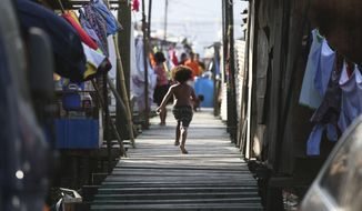 FILE - In this Nov. 15, 2018, file photo, a girl runs towards their home at Port Moresby, Papua New Guinea. More than 20 people including pregnant women and children have been killed in recent tribal violence in Papua New Guinea, media reported on Wednesday, July 10, 2019. The death toll and dates of the violence in the remote highland province of Hela varied in reports by Australian Broadcasting Corp. and the Post-Courier newspaper. (AP Photo/Aaron Favila, File)