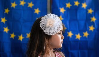 FILE - In this Sunday, May 26, 2019 file photo, a girl waits for her mother to vote in the European Elections and a referendum called by president Iohannis on corruption topics, backdropped by voting cabins with curtains depicting the European Union flag in Baleni, Romania. Romania's president says on Wednesday, July 10 the country's government is ignoring the will of its own citizens by not adopting anti-corruption recommendations made by a European anti-graft body. (AP Photo/Andreea Alexandru, File)
